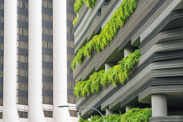 Moderne wolkenkratzerwand mit grünpflanzenterrassen in singapur-stadt