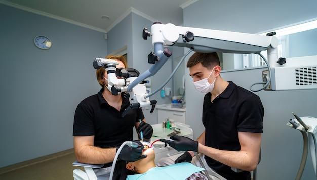 Moderne zahnarztpraxis mit stuhl und werkzeugen. mikroskop in der stomatologie. zahnmedizin, medizin, medizinische geräte und stomatologiekonzept.