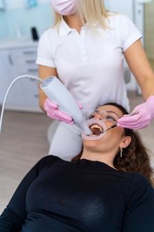 Moderne zahnarztpraxis mit stuhl und werkzeugen. mikroskop in der stomatologie.