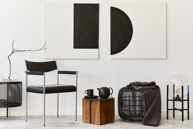 Moderne zusammensetzung des wohnzimmerinnenraums mit designschwarzstuhl, holzwürfel, rattan-hocker, kommode, lampe, kunstgemälden und eleganten accessoires in stilvoller wohnkultur.