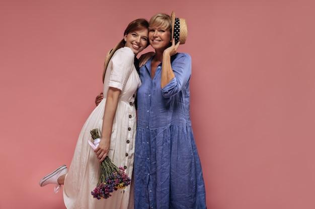 Moderne zwei damen mit kühler kurzer frisur in den trendigen kleidern lächelnd, umarmt und hält blumenstrauß und strohhut auf lokalisiertem hintergrund.