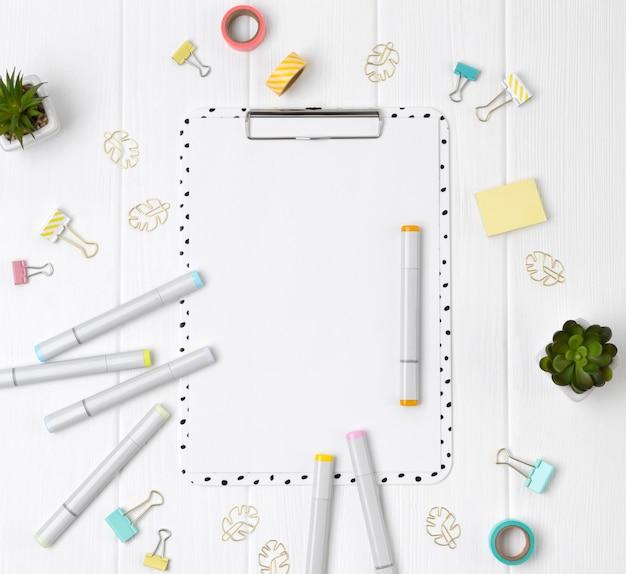 Moderne zwischenablage mit leerem blatt und markierungen, clip, klebebandbindern und pflanzen auf einem weißen holztisch.