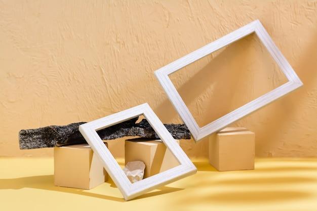 Moderner abstrakter lebensstilhintergrund: beton, leere bilderrahmen, steine und baumrinde im schatten der blätter. platz für text