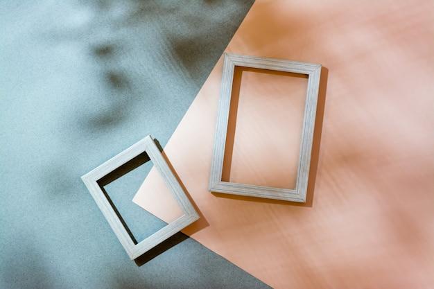 Moderner abstrakter lebensstilhintergrund: karton und leere bilderrahmen in weichen schatten aus den blättern. ansicht von oben. platz für text