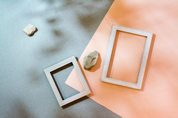 Moderner abstrakter lebensstilhintergrund: pappe, leere bilderrahmen und steine in weichen schatten aus den blättern. ansicht von oben. platz für text