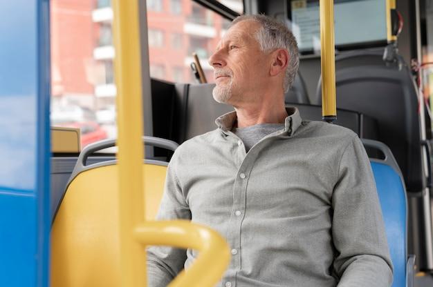 Moderner älterer mann, der im bus sitzt