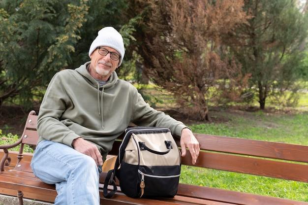 Moderner älterer mann, der im park entspannt