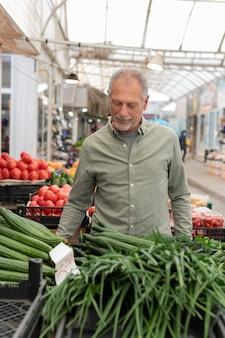 Moderner älterer mann, der lebensmitteleinkauf tut