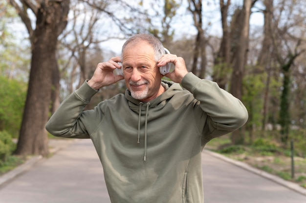 Moderner älterer mann, der musik in einem headset hört