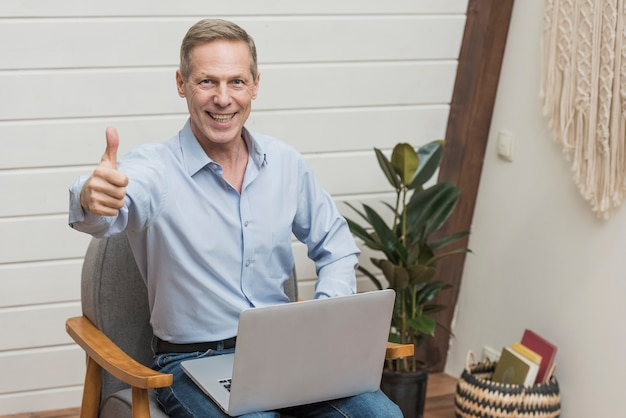 Moderner älterer mann der vorderansicht, der einen laptop hält
