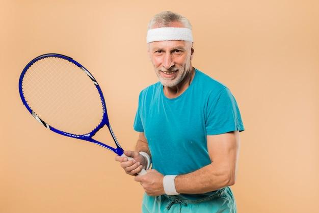 Moderner älterer mann mit tennisschläger