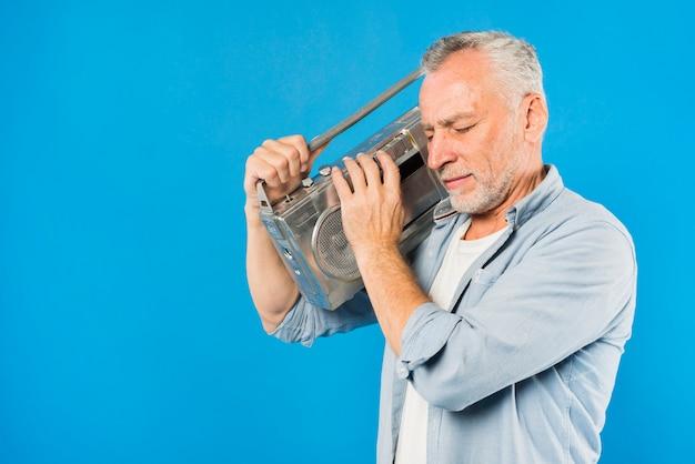 Moderner älterer mann mit weinleseradio