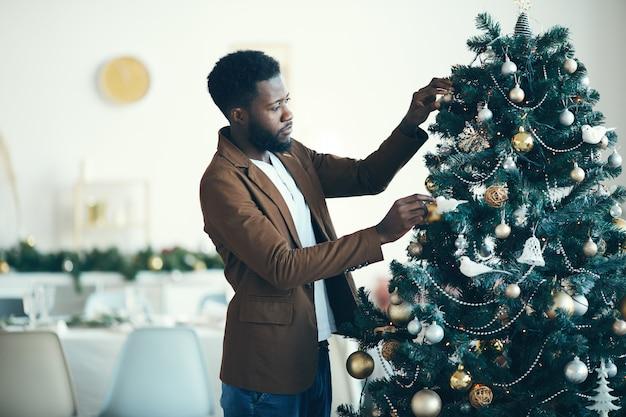 Moderner afrikanischer mann, der weihnachtsbaum verziert