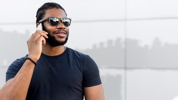 Moderner afroamerikanermann, der am telefon mit kopienraum spricht