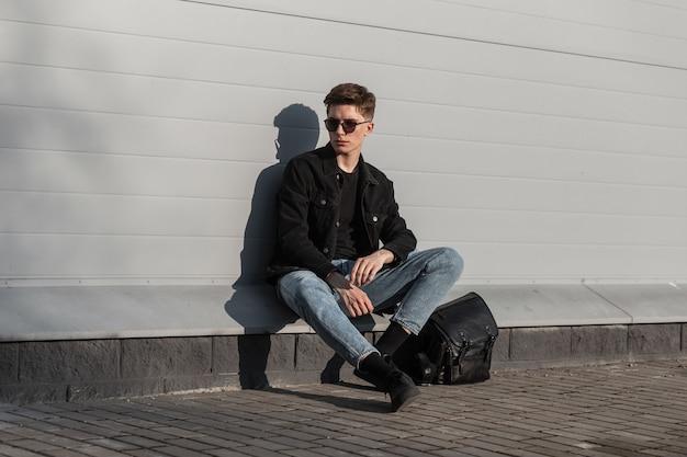 Moderner amerikanischer junger mann in modischer sonnenbrille in stilvoller, lässiger jeanskleidung