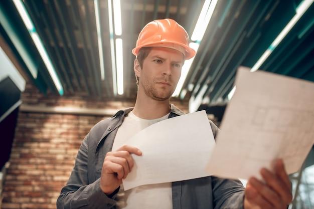 Moderner ansatz. attraktiver mann mit schutzhelm, der sich konstruktionszeichnungen im beleuchteten raum genau ansieht, der vor backsteinmauerhintergrund steht