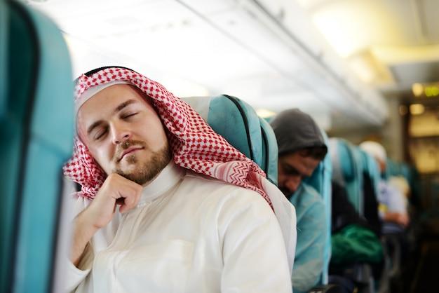 Moderner arabischer geschäftsmann innerhalb des flugzeuges