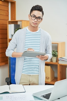 Moderner arbeiter mit tablette im büro