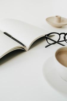 Moderner arbeitsbereich des home office schreibtisch mit notizbuch, tasse kaffee, gläser auf weißem hintergrund