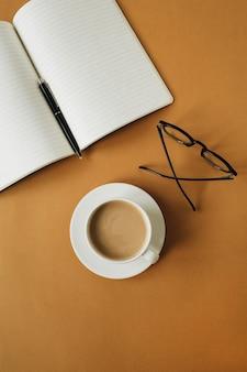 Moderner arbeitsbereich des schreibtischs zu hause mit notizbuch, tasse kaffee, gläsern auf ingwer