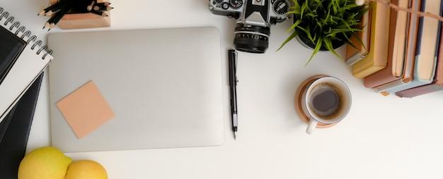Moderner arbeitsbereich mit laptop, briefpapier, kamera, büchern und dekorationen auf weißem tisch