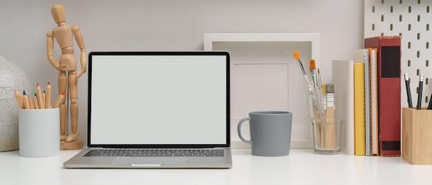 Moderner arbeitsbereich mit modell-laptop, schreibwaren, malwerkzeugen und dekorationen