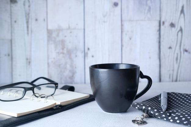 Moderner arbeitsbereich mit notizblock und brille auf dem tisch