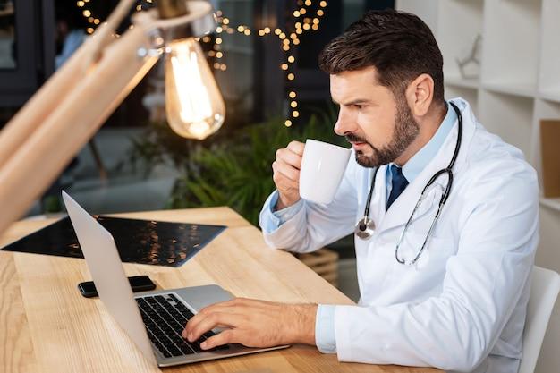 Moderner arbeitsplatz. hart arbeitender kluger männlicher arzt, der tee trinkt und einen laptop benutzt, während er nach notwendigen informationen sucht