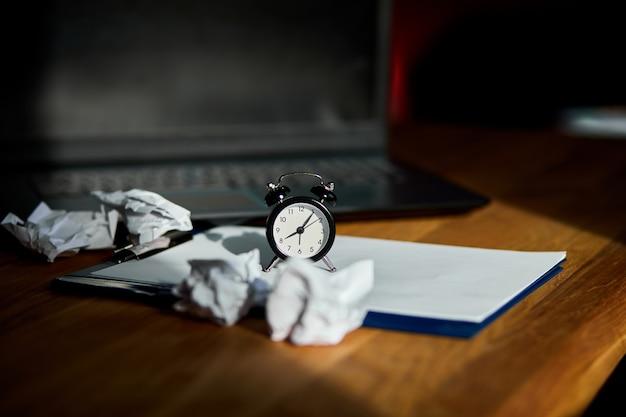 Moderner arbeitsplatz, hölzerner schreibtisch im harten licht, sonnendurchflutet mit uhr, blatt papier, laptop, notizbuch, zerknitterten papierkugeln, änderung ihrer denkweise, plan b, zeit, um neue ziele zu setzen, geschäft