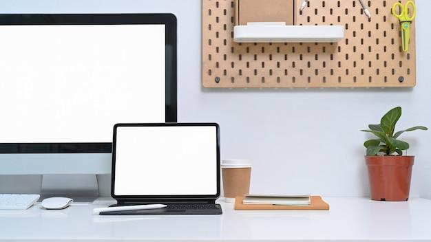 Moderner arbeitsplatz mit computer, digitalem tablet, zimmerpflanze und bürobedarf auf weißem tisch.