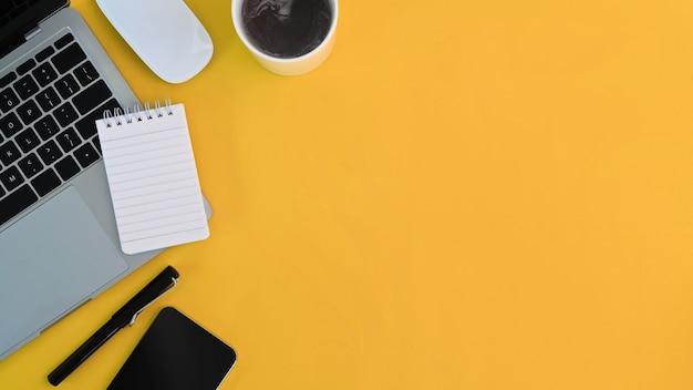Moderner arbeitsplatz mit computerlaptop, kaffeetasse, notizbuch, smartphone und kopienraum auf gelbem hintergrund.
