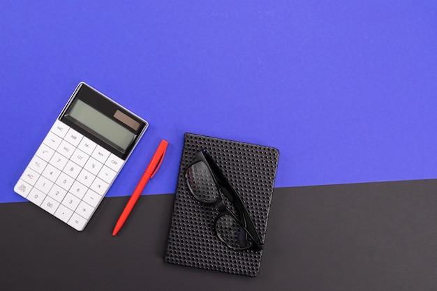 Moderner arbeitsplatz mit dem notizbuch, stift und taschenrechner lokalisiert auf hintergrund des blauen schwarzen