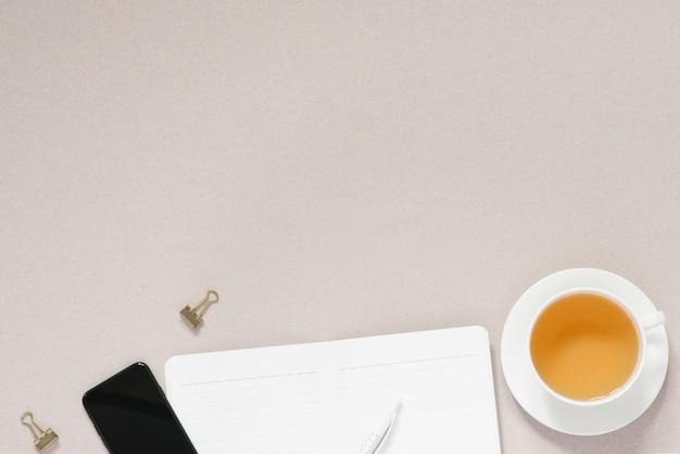 Moderner arbeitsplatz mit einer tasse tee. bürooberteil mit tagebuch, stift und telefon. arbeitsplatzbanner mit kopierplatz