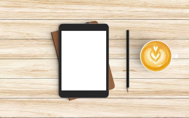 Moderner arbeitsplatz mit kaffeetasse, notizbuch, tablette oder smartphone und bleistift auf holz