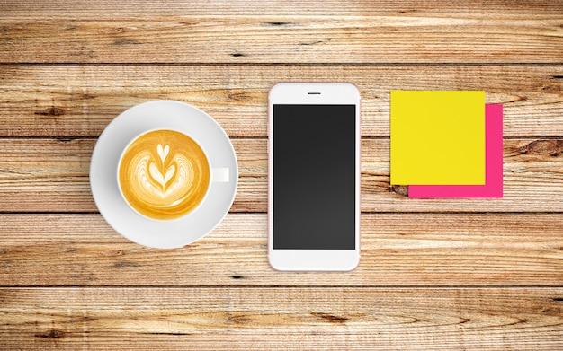 Moderner arbeitsplatz mit kaffeetasse, notizbuch, tablette oder smartphone und tastatur auf holz