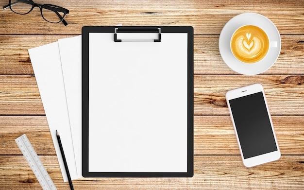 Moderner arbeitsplatz mit kaffeetasse, papier, notizbuch, tablette oder smartphone und klemmbrett auf holz