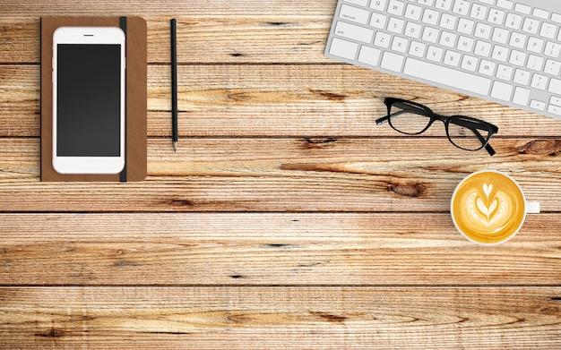 Moderner arbeitsplatz mit kaffeetasse, papier, notizbuch, tablette oder smartphone und tastatur auf holz