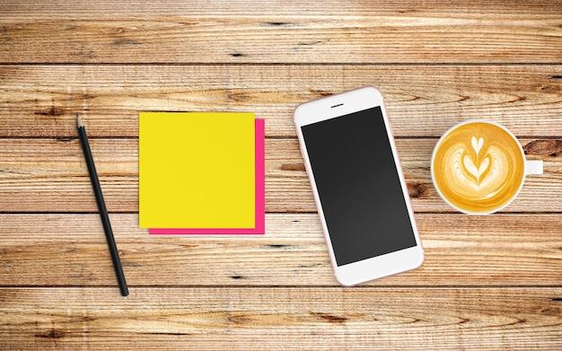 Moderner arbeitsplatz mit kaffeetasse und tablette oder smartphone auf holz