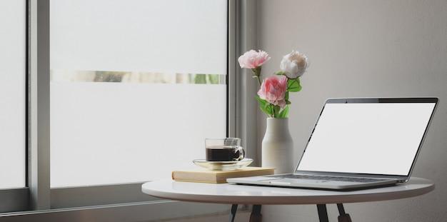 Moderner arbeitsplatz mit laptop-computer und blumendekorationen auf weißer tabelle
