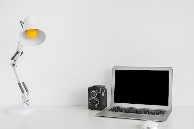 Moderner arbeitsplatz mit laptop und alter filmkamera