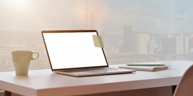 Moderner arbeitsplatz mit laptop- und stadtansichthintergrund