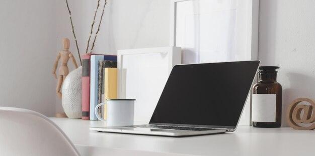 Moderner arbeitsplatz mit offener laptop-computer mit bürozubehör und kopienraum