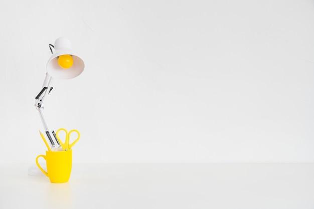 Moderner arbeitsplatz mit schreibtischlampe und gelber tasse
