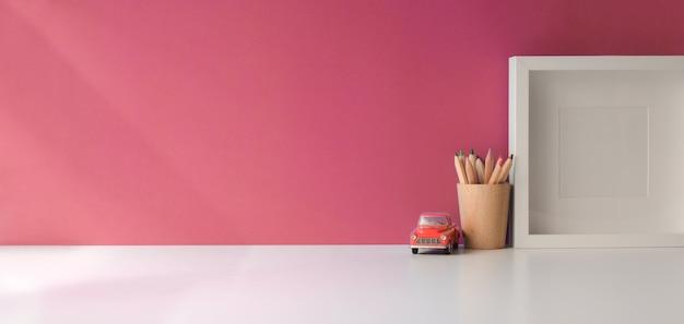 Moderner arbeitsplatz mit verspotten herauf rahmen- und kopienraum auf weißem holztisch und rosa wand