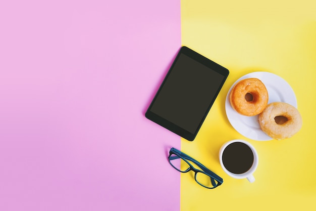 Moderner arbeitsplatz, schwarzer kaffee, schaumgummiringe, augengläser mit tablette auf pastellhintergrund