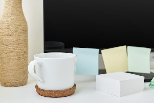 Moderner arbeitsplatzhintergrund. arbeitsplatz mit einer tasse kaffee, büromaterial und haftnotizen auf dem tisch