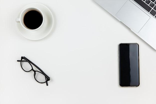 Moderner arbeitsraum, draufsicht. laptop, kaffee, smartphone, brille auf weißem hintergrund, kopierraum, flache lage
