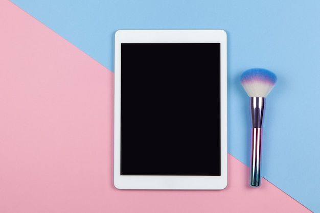 Moderner arbeitsraum von visagiste, draufsicht. tablette, make-up-pinsel auf zweifarbigem hintergrund