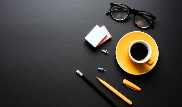 Moderner arbeitstisch im schwarzen farbhintergrund. kreativitätsraum