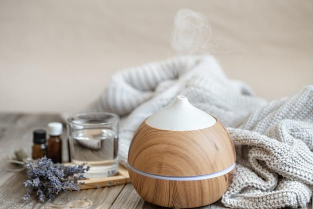 Moderner aromaöldiffusor auf holzoberfläche mit strickelement, wasser und lavendelöl.